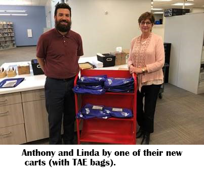 HCPL employees Anthony and Linda, standing by a cart full of TAE bags